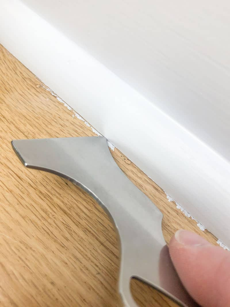 scoring seam between baseboards and floor with painter's tool