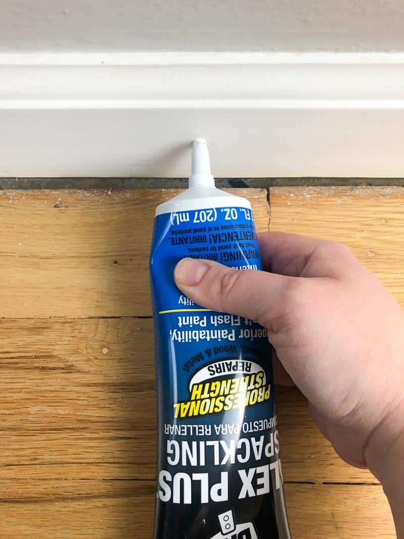 filling nail holes in baseboards with spackle