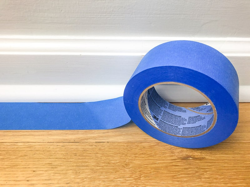 applying painter's tape to floor before painting baseboards