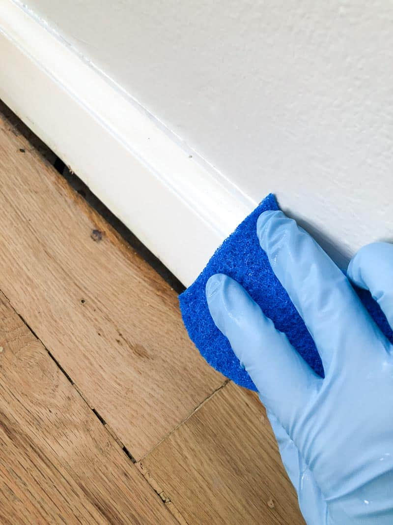wiping down baseboards before painting