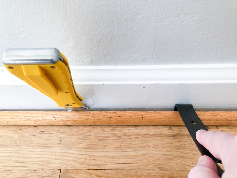 using putty knife and small pry bar to remove quarter round without damaging baseboards