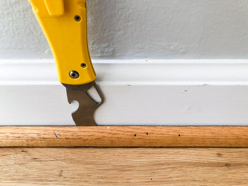 putty knife between quarter round and baseboards