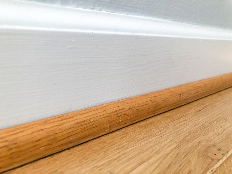 oak quarter round trim on white baseboards