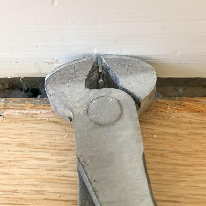 nail puller clamped around base of nail in baseboards