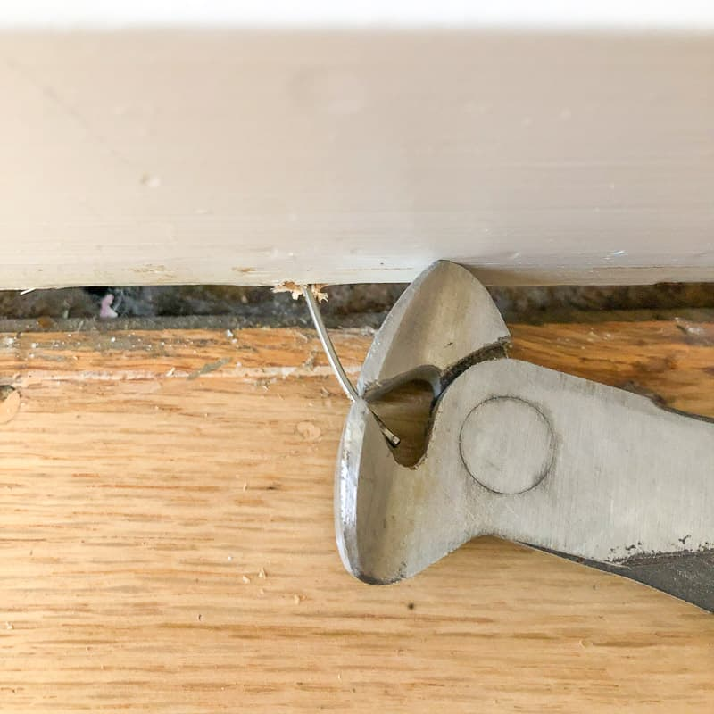 using a nail puller to remove nails from baseboards after quarter round trim is removed