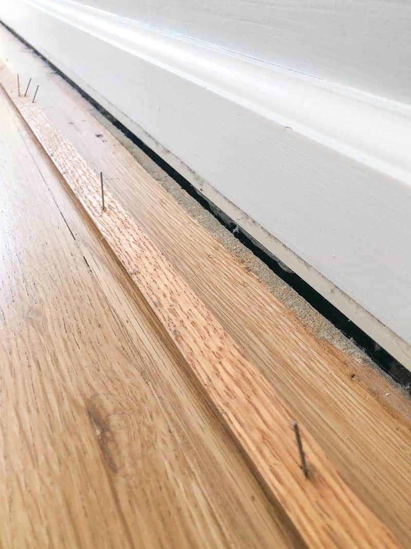 quarter round trim removed from baseboards, exposing gap between floor and wall