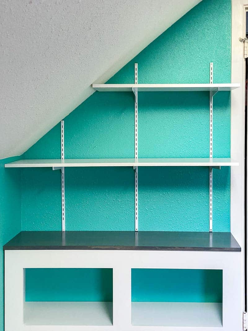 adjustable wall mounted shelving installed on wall with sloped ceiling