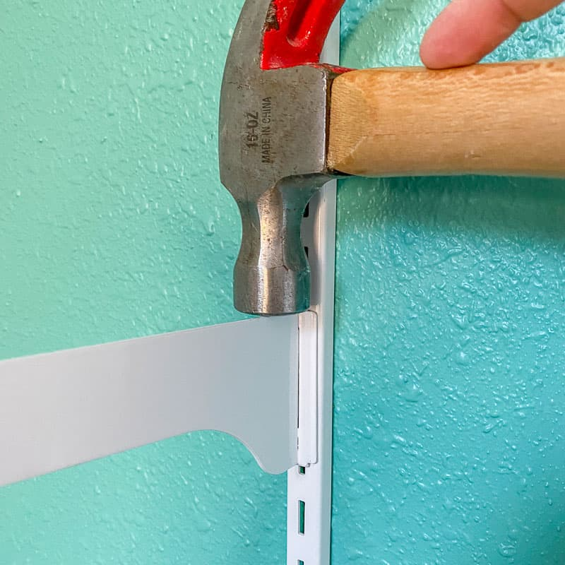 hammering shelf bracket into vertical standard on wall