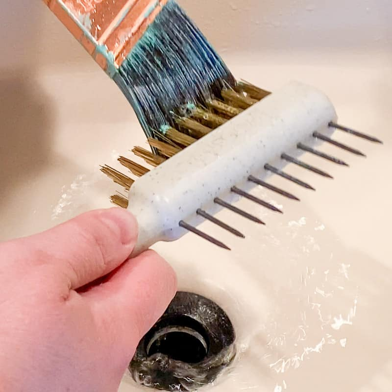 using fine bristles from brush comb to remove dried paint from outside of paint brush