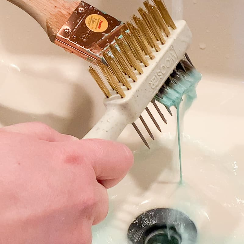 using a brush comb to clean paint out of a paint brush