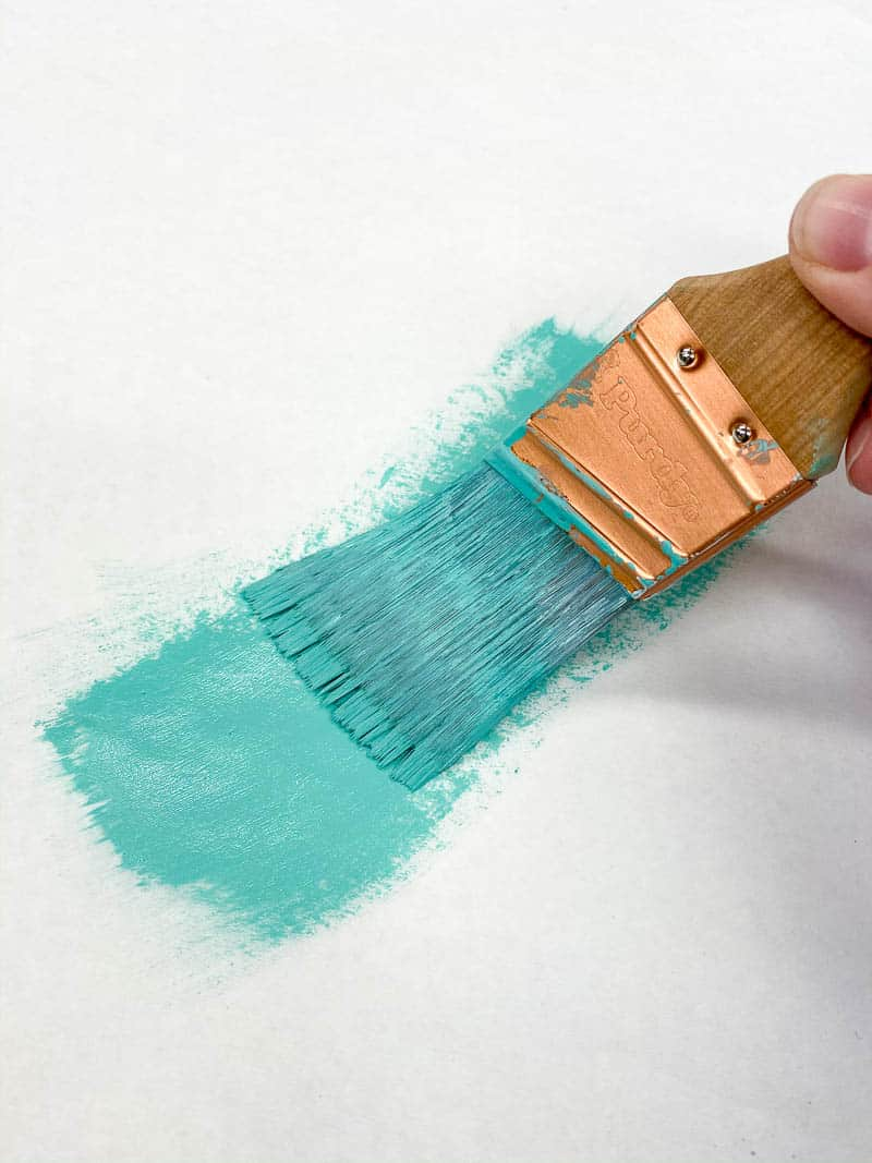removing excess paint from brush with paper