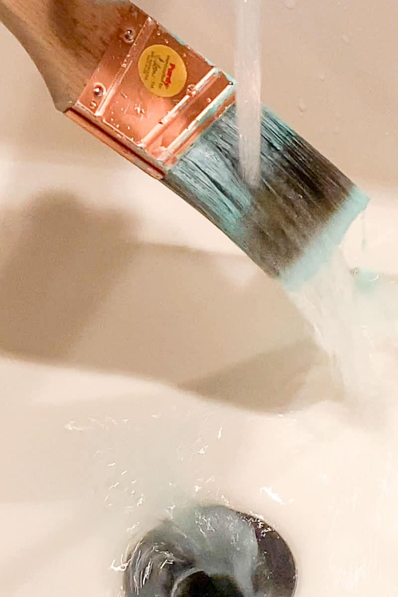 rinsing paint brush in running water