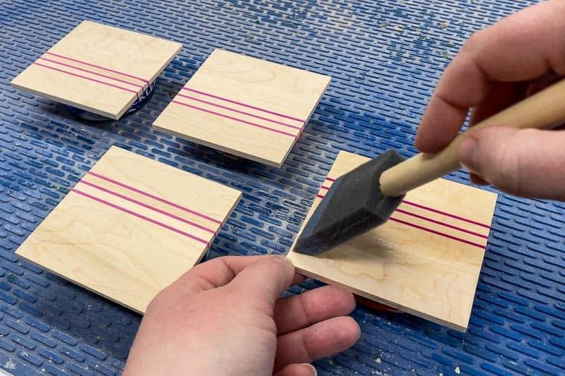 applying polycrylic finish to DIY wood coasters with a foam brush