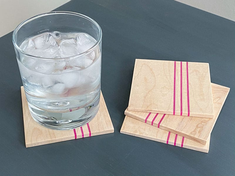 DIY wood coasters with pink stripes on gray table with glass of ice water