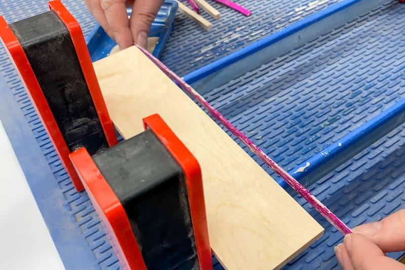 adding pink wood veneer stripe to DIY wood coasters during glue up