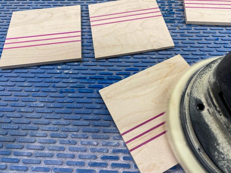 sanding DIY wood coasters on a blue silicone mat