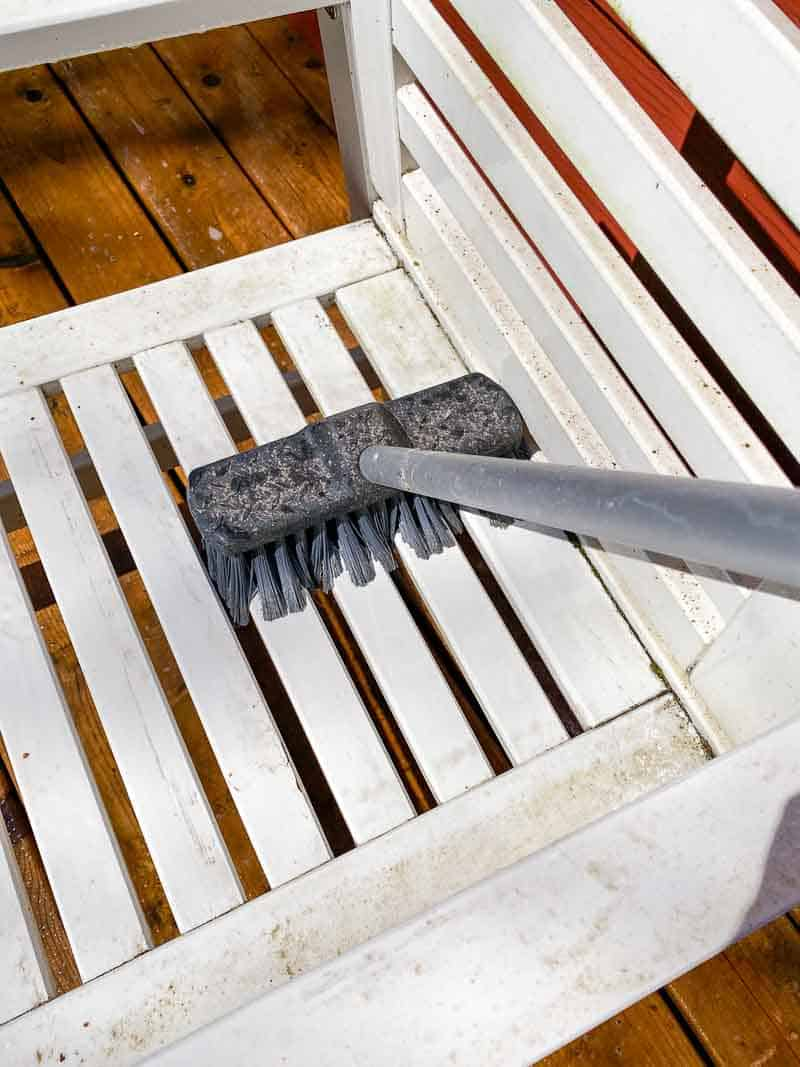 scrubbing outdoor furniture with cleaner