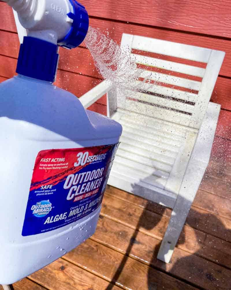 spraying cleaner on outdoor furniture