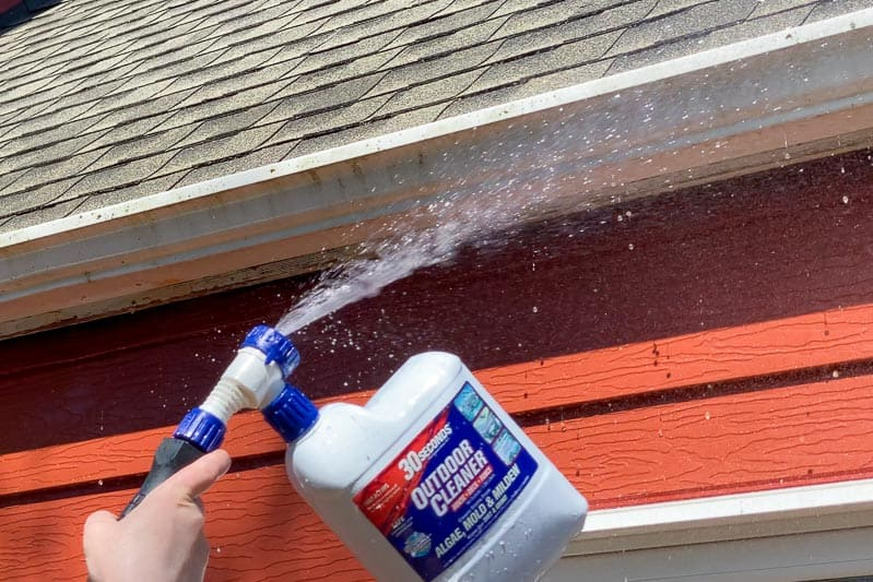 spraying cleaner on outside of gutters