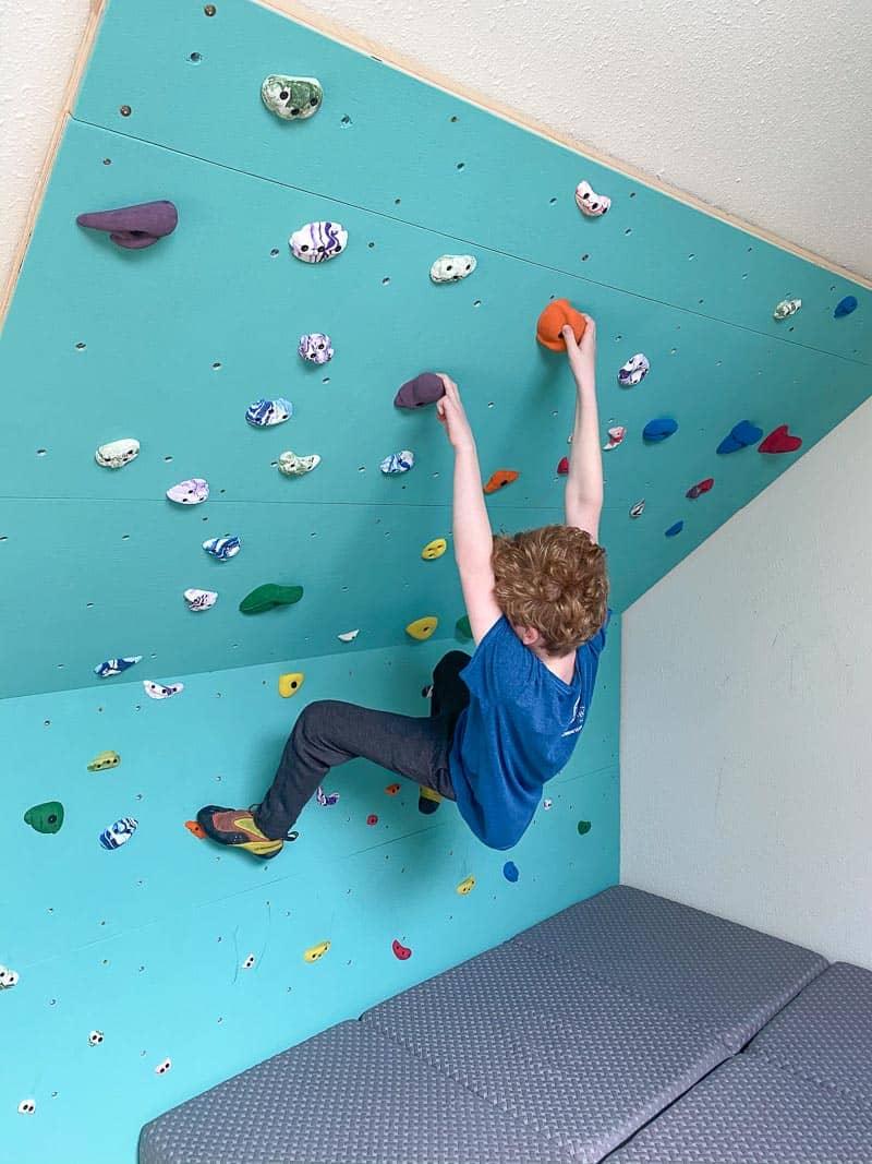 kid hanging on home climbing wall