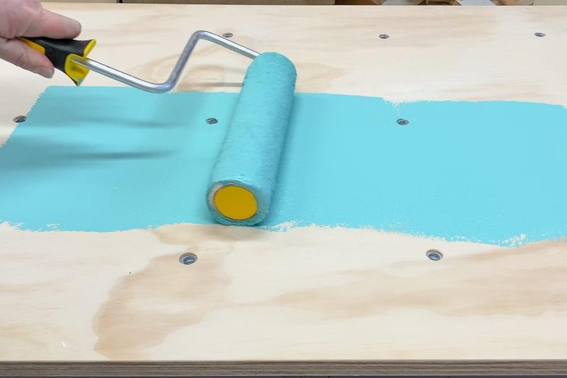 rolling epoxy paint onto climbing wall panel