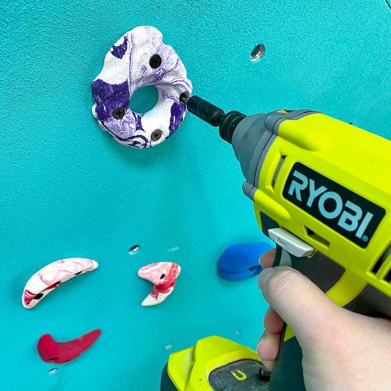 screwing climbing hold into DIY climbing wall