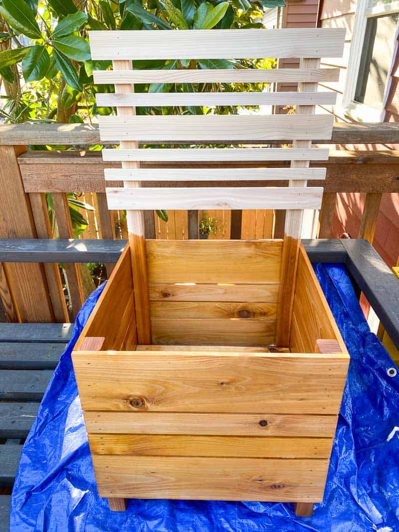 applying outdoor wood stain to DIY planter box with trellis