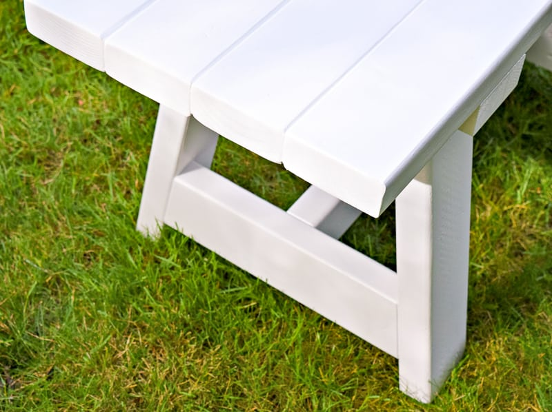 close up of white 2x4 bench on grass