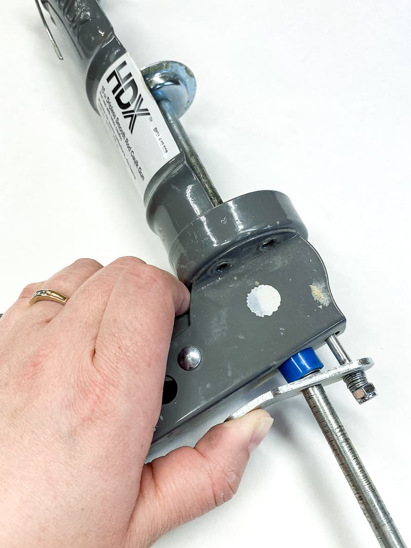 how to release the pressure on a caulk gun to remove the tube