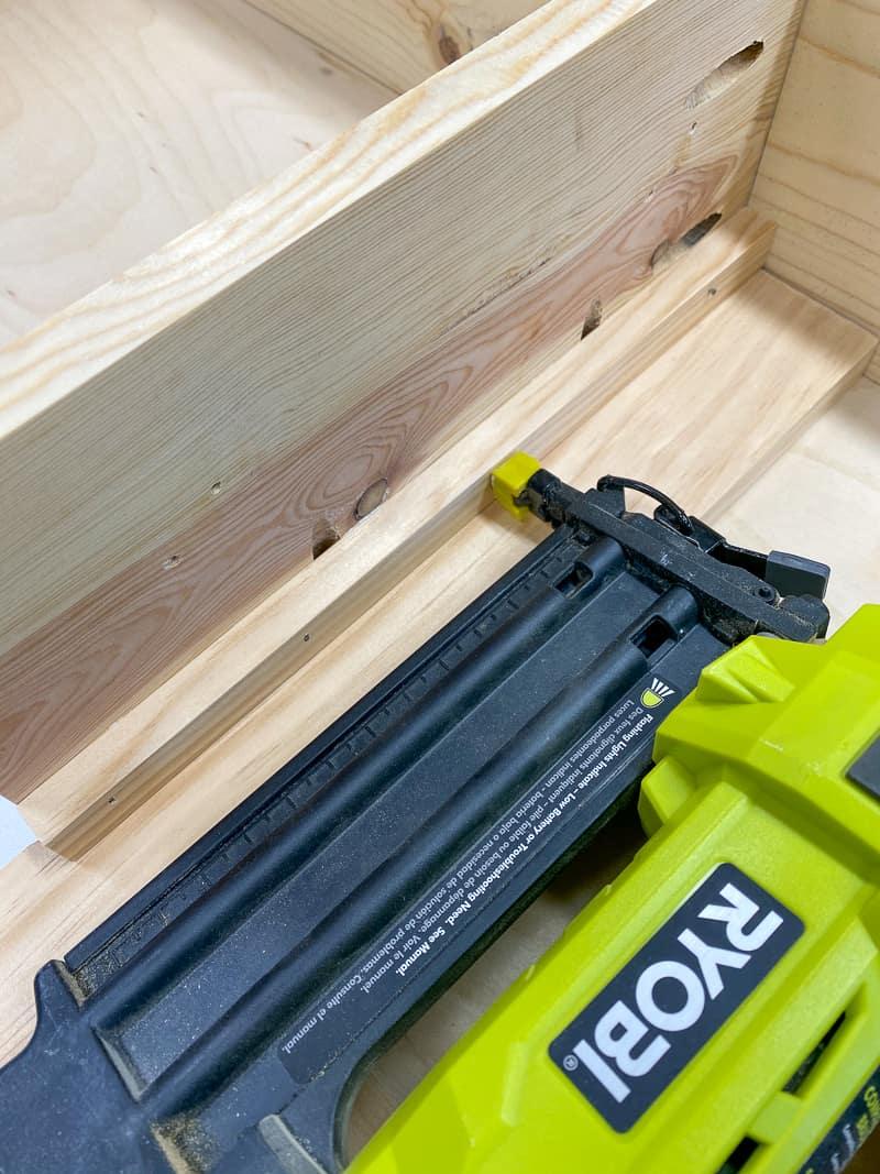 attaching bin supports to sides of Trofast shelf with Ryobi brad nailer