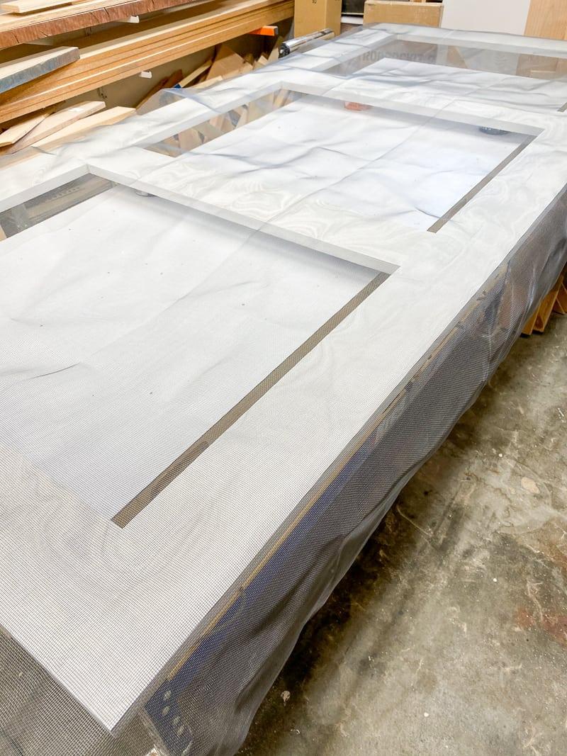 mesh screen material laying on DIY screen door frame
