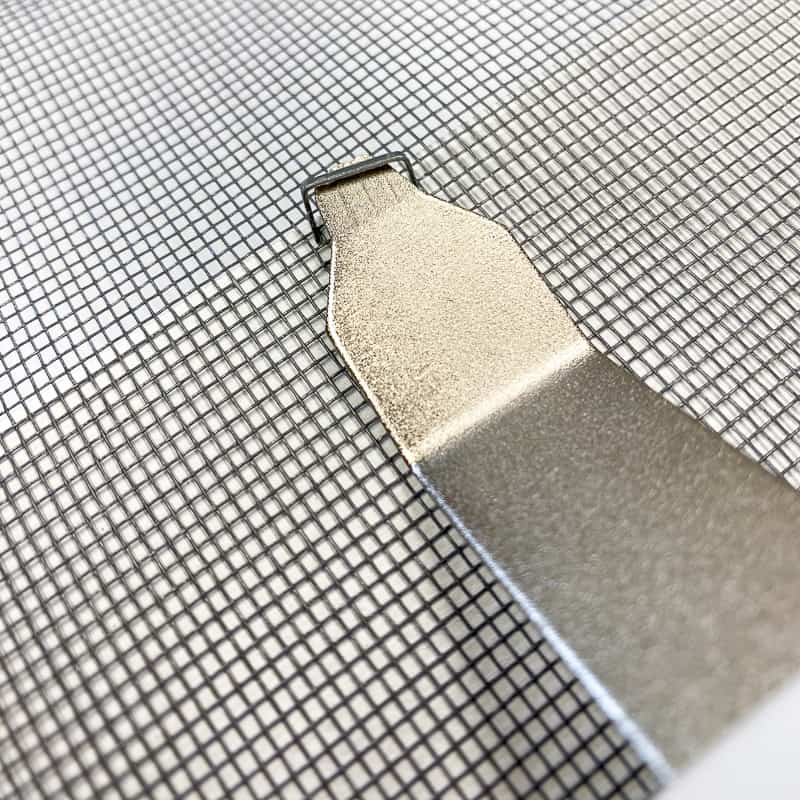 removing a staple from the mesh screen on a DIY screen door