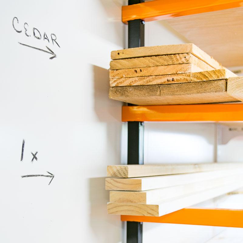 white hardboard installed on wall behind lumber rack