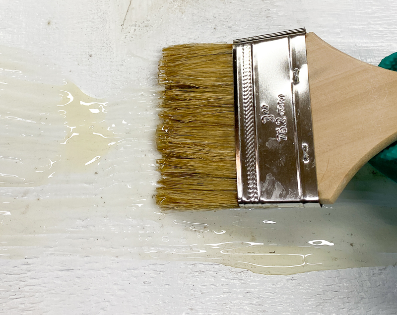 chip brush smoothing out paint stripper