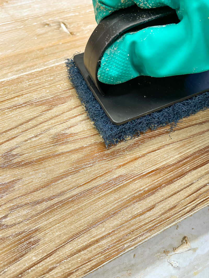 using a scrub brush to remove the last bits of paint from wood