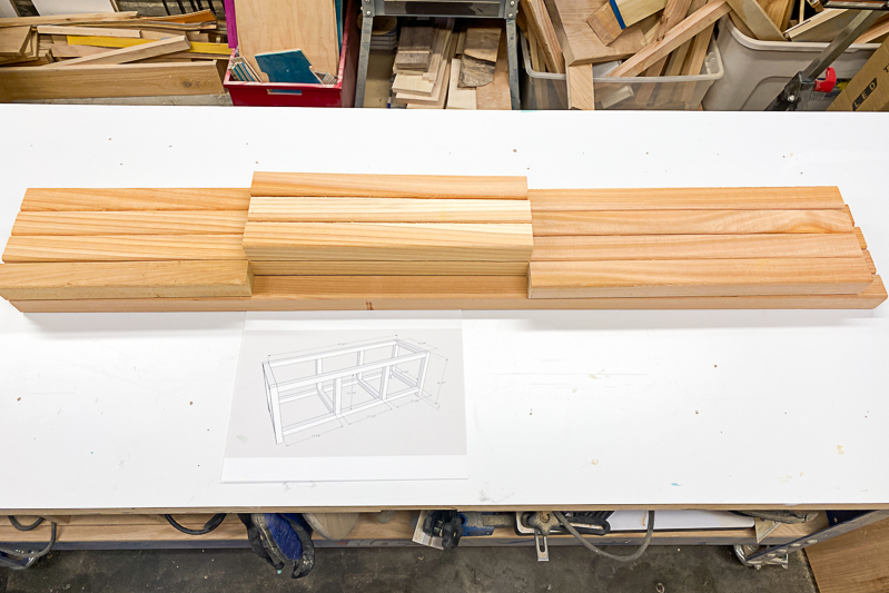 DIY outdoor storage box frame pieces cut out and arranged on a workbench