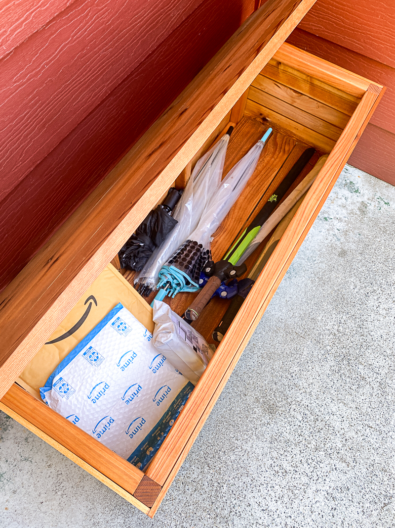 packages hidden on front porch inside DIY outdoor storage box