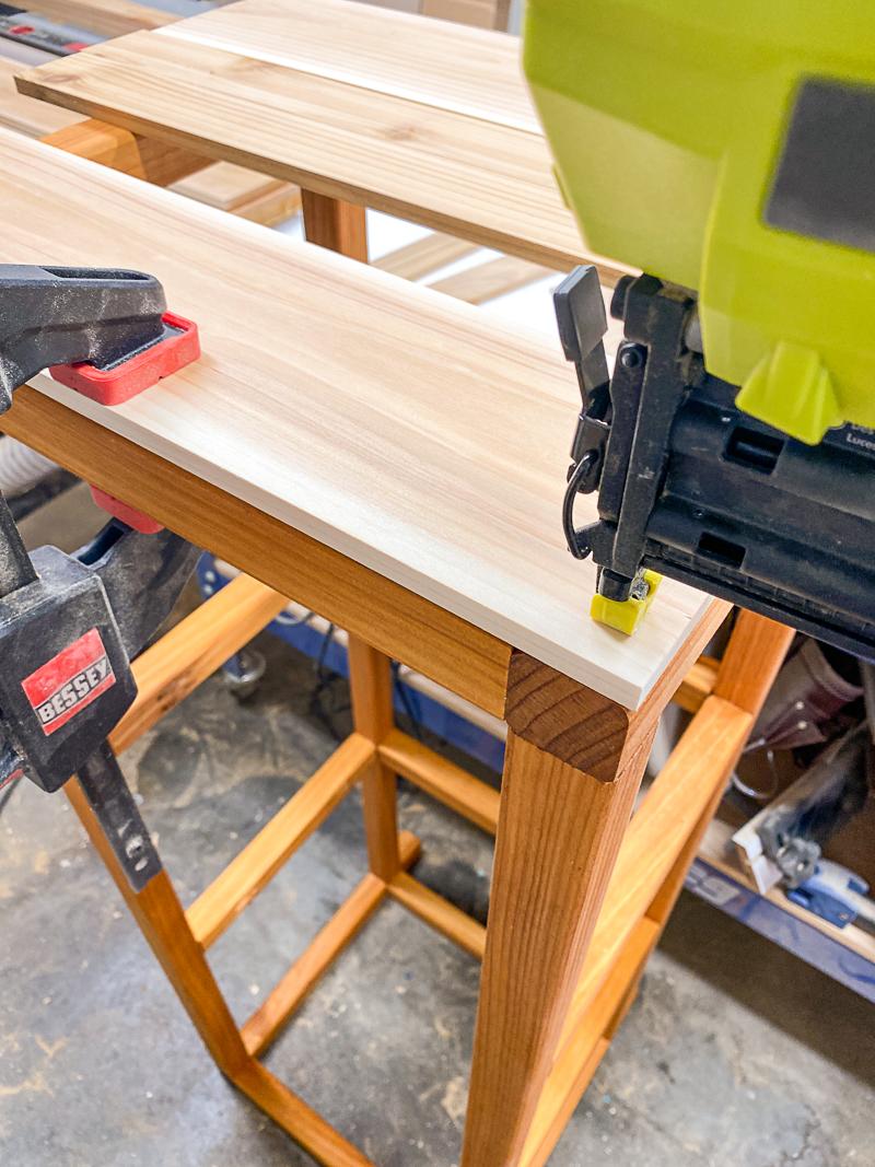 nailing first slat onto frame of DIY outdoor storage box