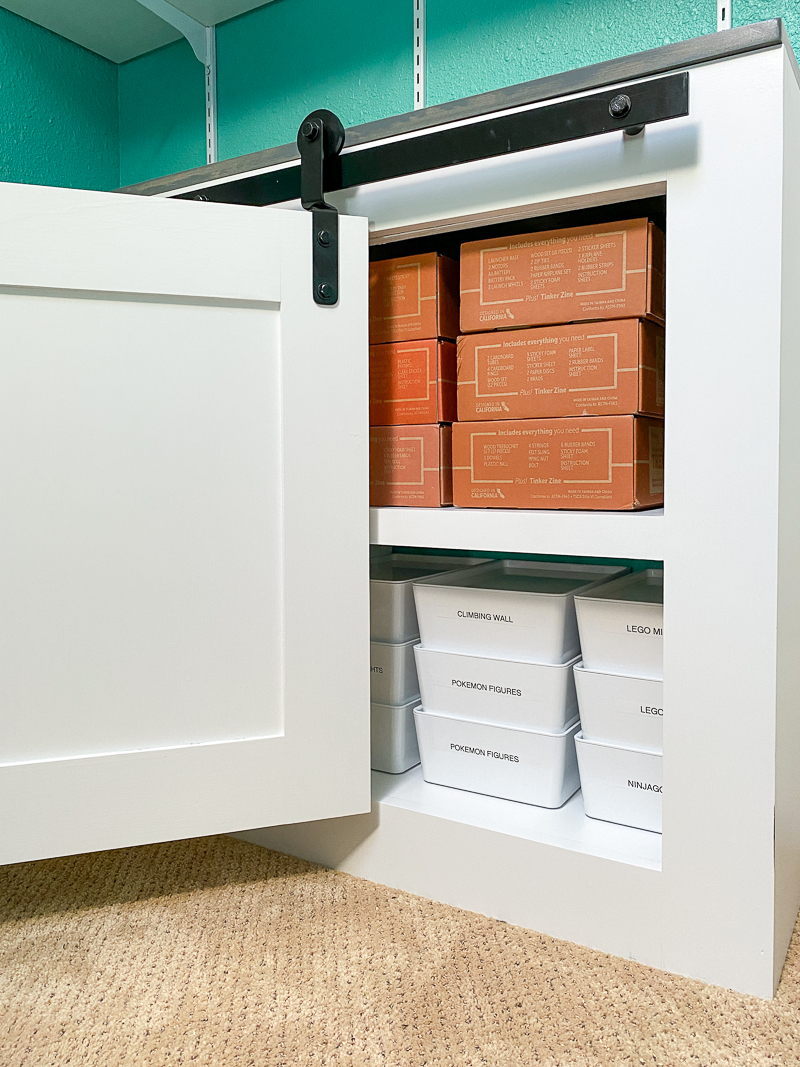 bifold barn doors partially opened to reveal organized bins inside cabinet