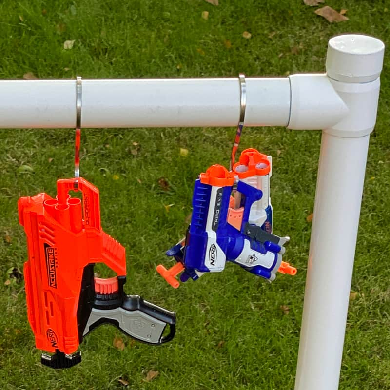 Nerf guns on hooks hanging from storage rack