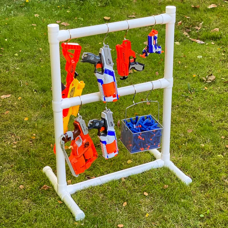 Nerf gun rack made of PVC pipe on a grassy lawn