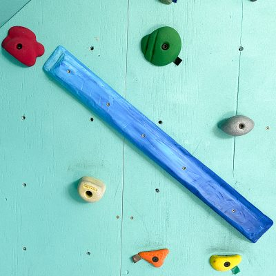long blue wooden climbing hold on wall