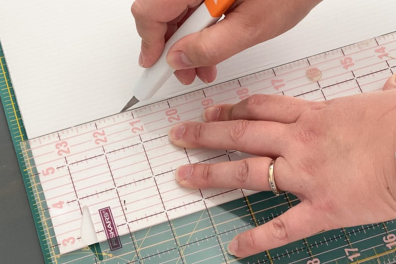 cutting out dividers from plastic corrugated board with a utility knife and ruler