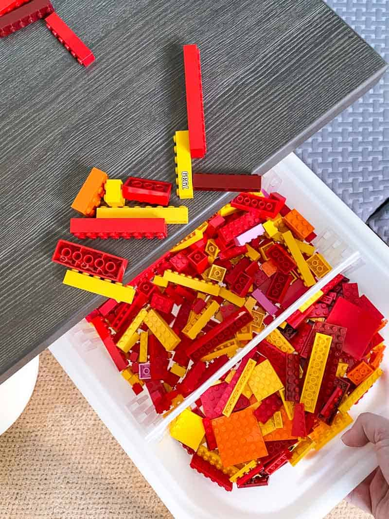 cleaning up Lego pieces by sliding them into a bin in the Lego desk