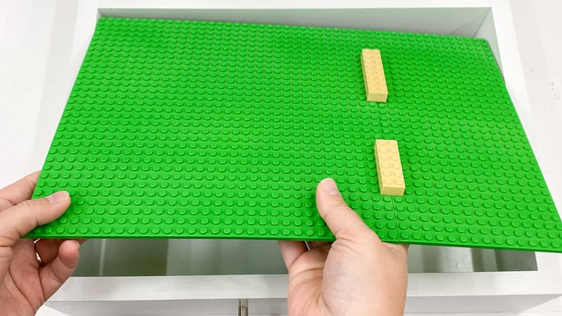 Large Lego pieces connecting two green base plates together