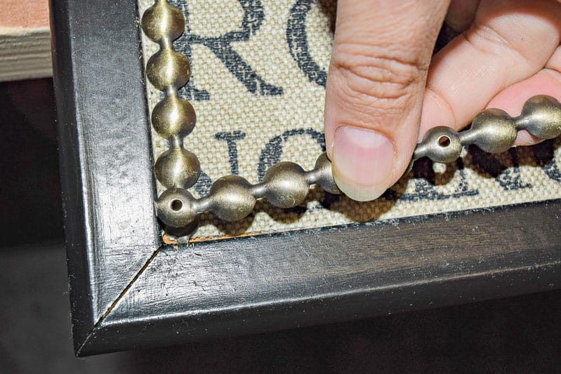 securing the corners of the nailhead trim on the DIY push pin travel map