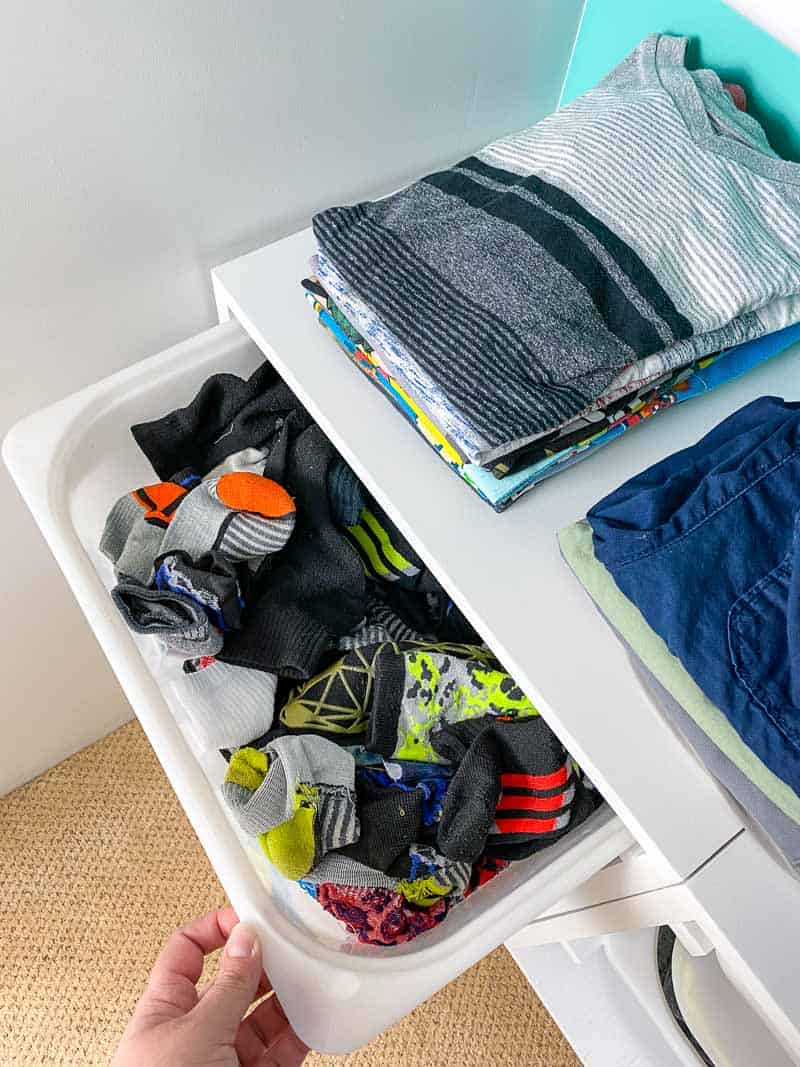 wall mount storage bins being used as a dresser with bins for socks and the top as a shelf
