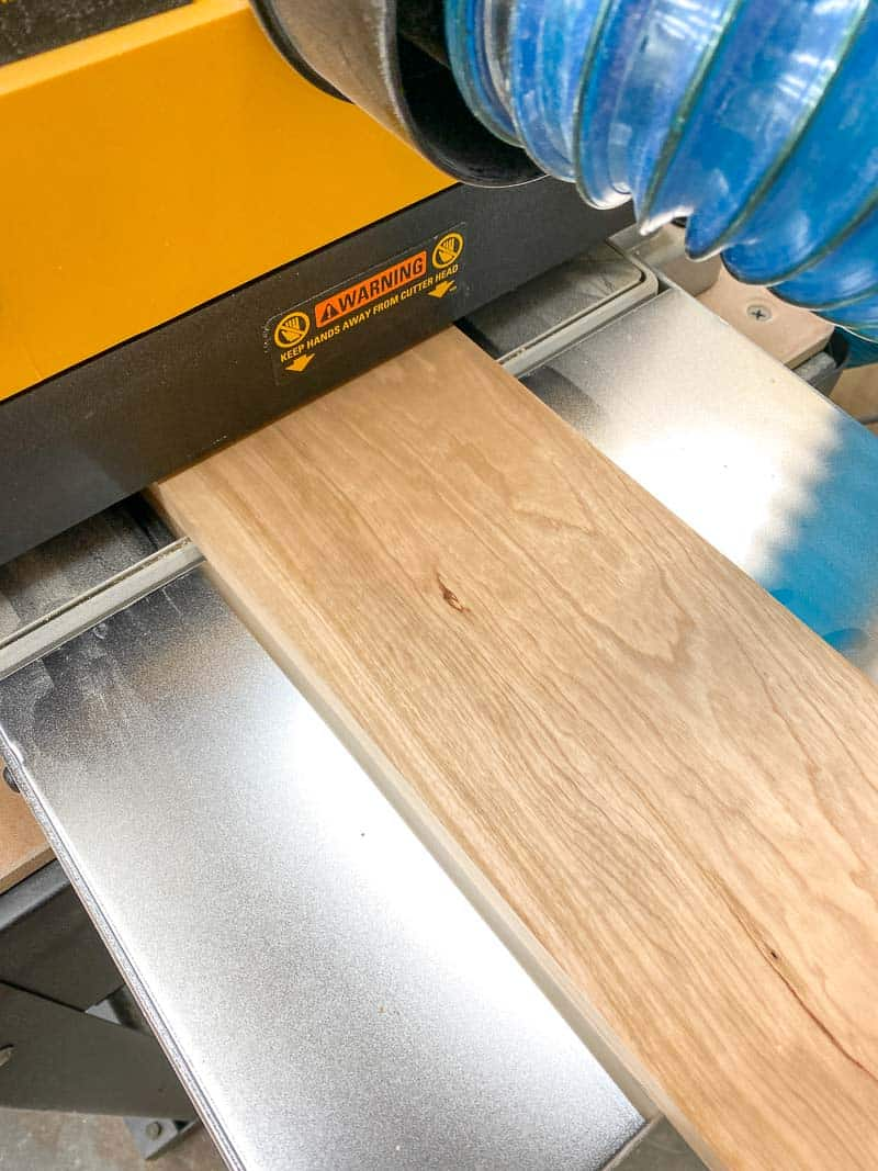 cherry wood board coming out of Dewalt thickness planer