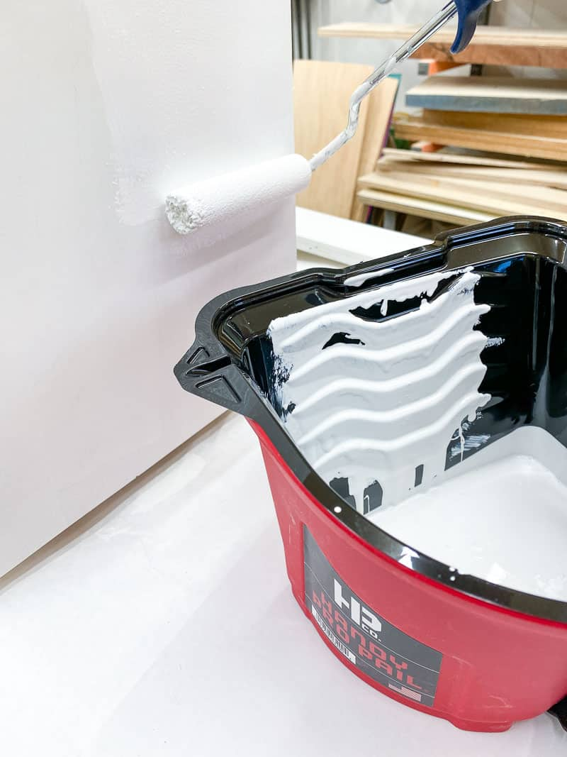 painting sides of wall mount storage bin frame with a roller