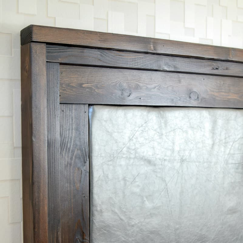 DIY upholstered headboard with dark wood trim